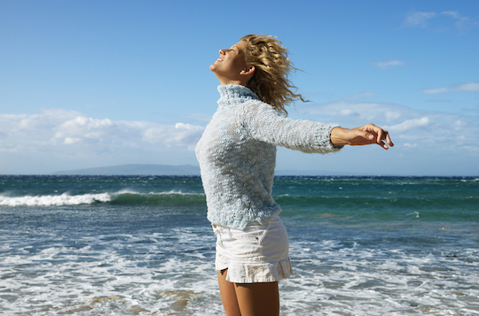 Pretty young blond woman standing on Maui, Hawaii beach with arms out to side and wind blowing hair